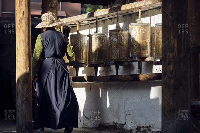 September 5, 2020: Back view of anonymous woman in stylish clothes turning Buddhist golden prayer wheels located in Sichuan