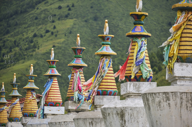 Traditional colorful Buddhist statues with multicolored ribbons located in green valley in Sichuan at daytime
