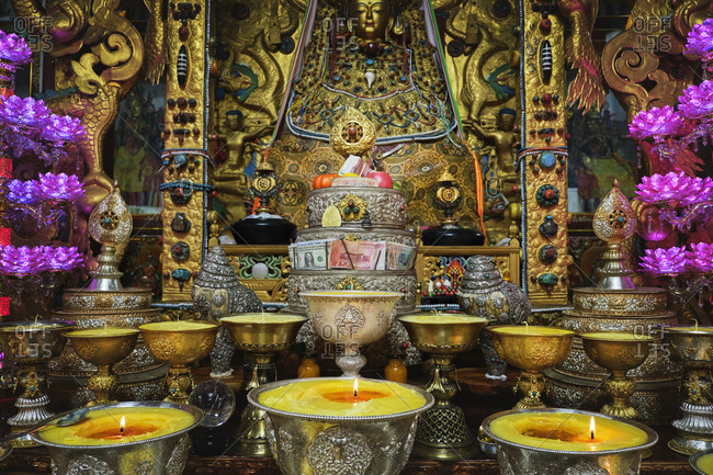 Golden decorative elements in Buddhist shrine with burning flames in praying holy place in China
