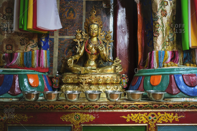 Interior of traditional oriental temple with golden figure of praying Buddha with metal bowls