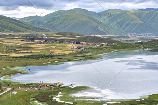 From above of peaceful pond with small village located on shore in green hilly valley in Sichuan province in China