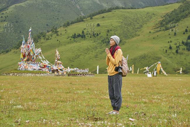 Full body of Asian female traveler standing with hands clasped in green village in China