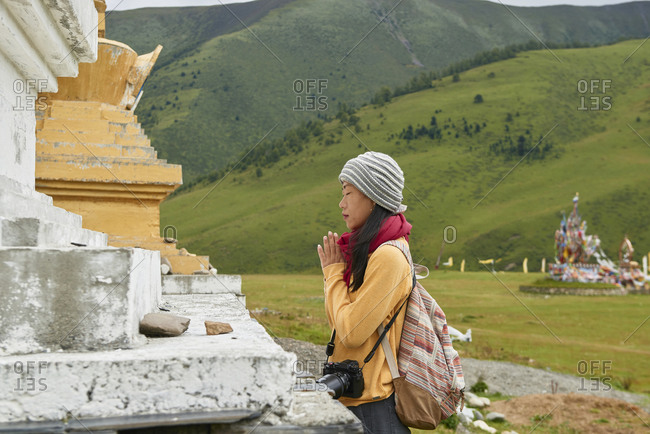 Asian female traveler standing with hands clasped in green village in China
