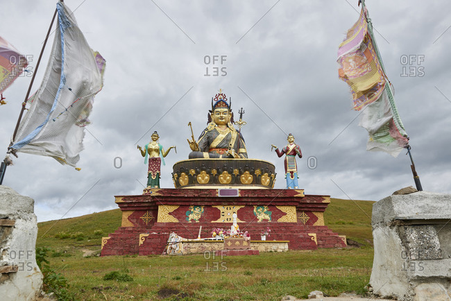 Low angle of Buddhist figures and waving flags located in sacred place in Sichuan province in China