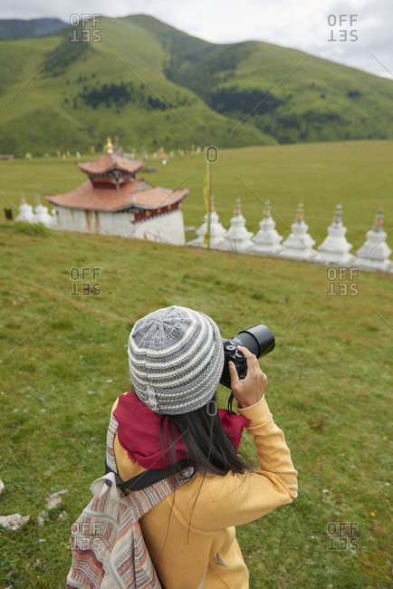 From above of anonymous female tourist shooting nature on photo camera while exploring oriental area with shrine in China