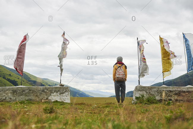 Low angle back view of anonymous woman standing with hands in pockets near waving flags and enjoying freedom in green hilly valley in China