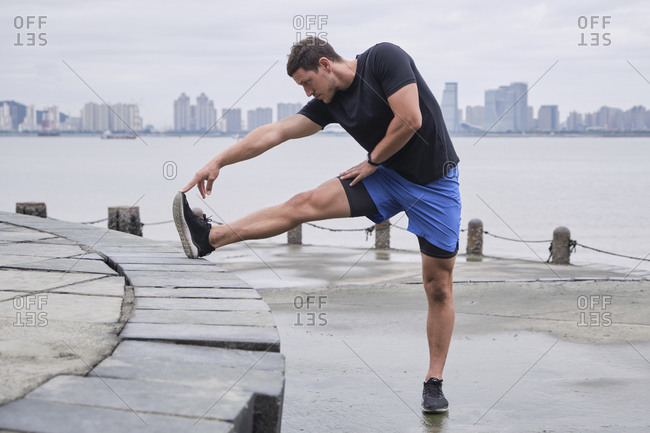 Concentrated male runner in sportswear standing on embankment and warming up while stretching legs and doing forward bend during workout