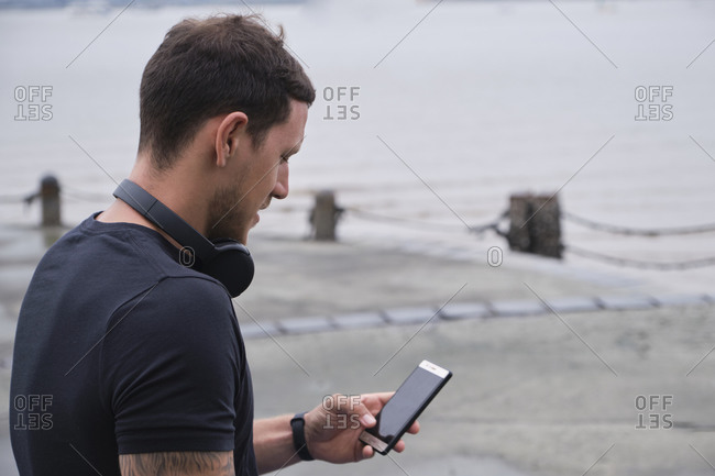 Male athlete sitting on stone border and surfing Internet on mobile phone while having break during workout in city