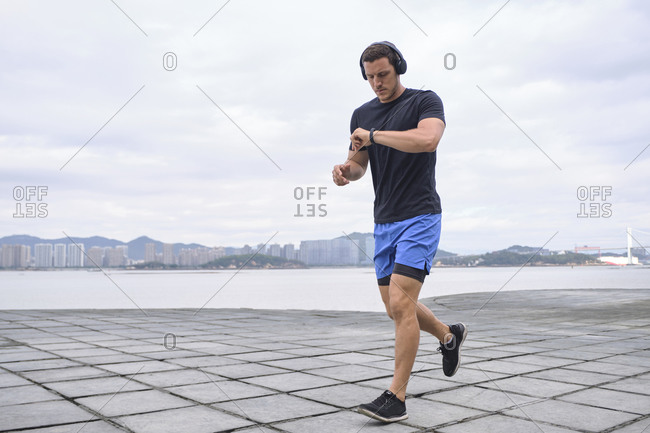 Serious male in headphones running along embankment and checking fitness tracker during cardio training
