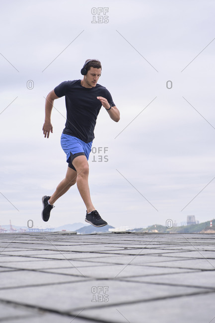 Ground level of focused male runner warming up and jumping above ground during training in city on cloudy day