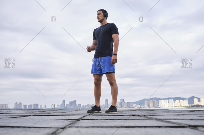 Ground level of determined male athlete in wireless headphones listening to music during workout while standing and looking away