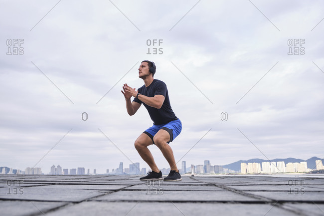Ground level of energetic male runner warming up body and jumping on street during cardio training while looking away