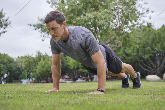 Low angle of strong male athlete doing push ups during training on green lawn in park