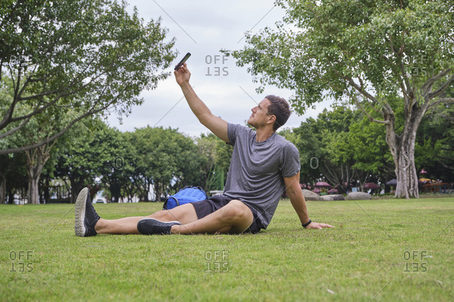 Side view of male athlete in activewear sitting on green meadow and warming up legs before training in city while taking selfie