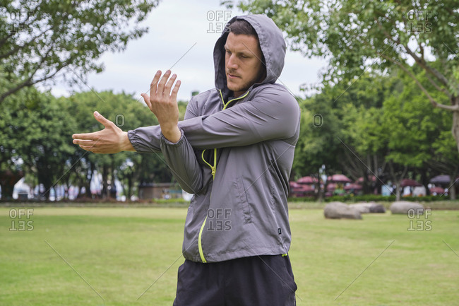 Concentrated male athlete in sportswear standing on park and warming up arms before workout in city