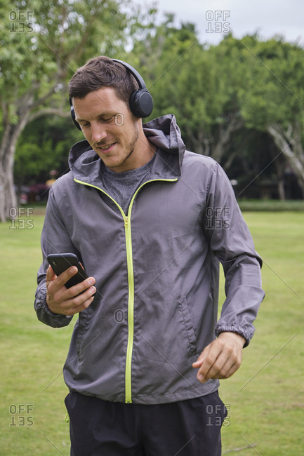 Smiling male runner in activewear and wireless headphones choosing songs from playlist on smartphone while preparing for training in park