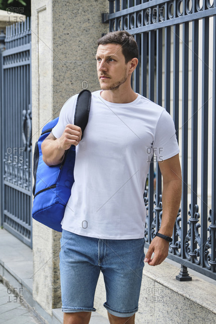 Determined male athlete in casual wear and with sports bag standing on street and looking away