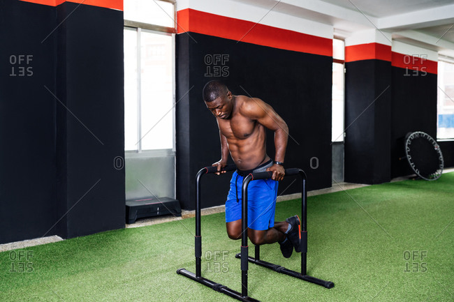 Concentrated African American male athlete doing exercises on parallel bars while pumping triceps during workout in gym
