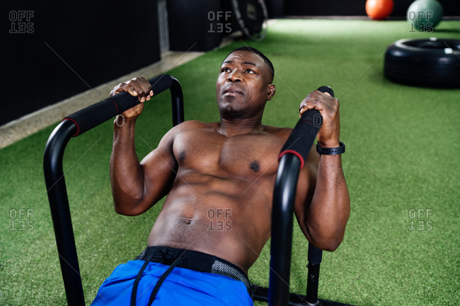 Muscular African American male with naked torso doing exercises on bars in gym while pumping biceps during intense training