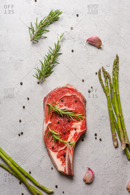Top view uncooked t bone beef steak garnished with black pepper and rosemary sprigs placed on table in kitchen