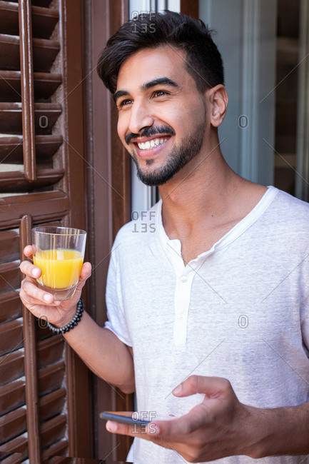 Young bearded male with glass of fruit juice and smartphone in hands standing near window and looking away with interest in morning time at home