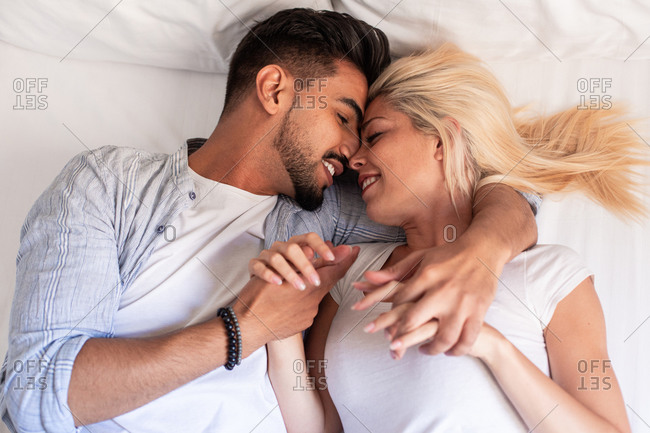 From above of cheerful couple in casual wear lying on soft bed at home and delicately cuddling with closed eyes
