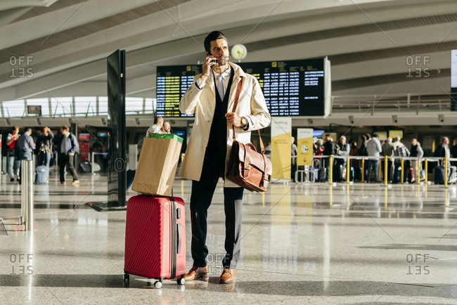 Man with dark hair in stylish clothes talking on phone while standing with suitcase in terminal of airport