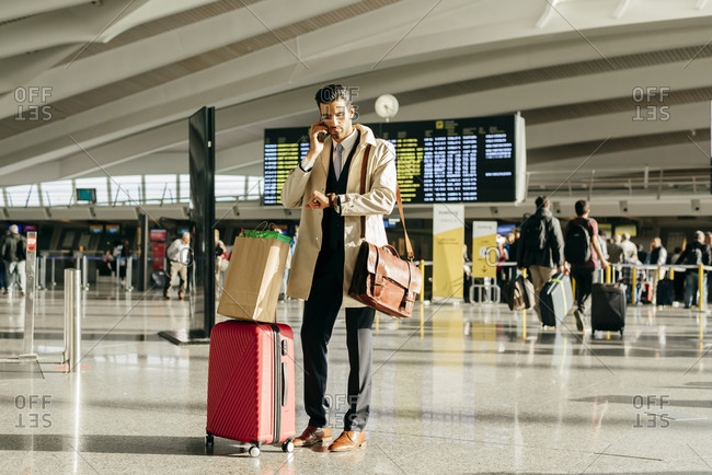 Man with dark hair in stylish clothes talking on phone and looking at watch while standing with suitcase in terminal of airport
