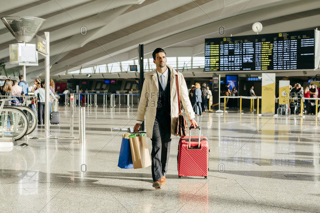 Man with dark hair in stylish clothes walking with suitcase in terminal of airport