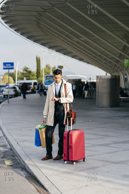 Young man with dark hair in trendy clothes with suitcase and shopping bags standing near modern airport and looking at watch in sunny day