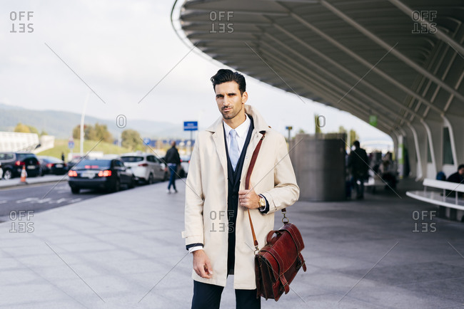 Man with dark hair in suit and coat looking at camera while standing near airport terminal at daytime