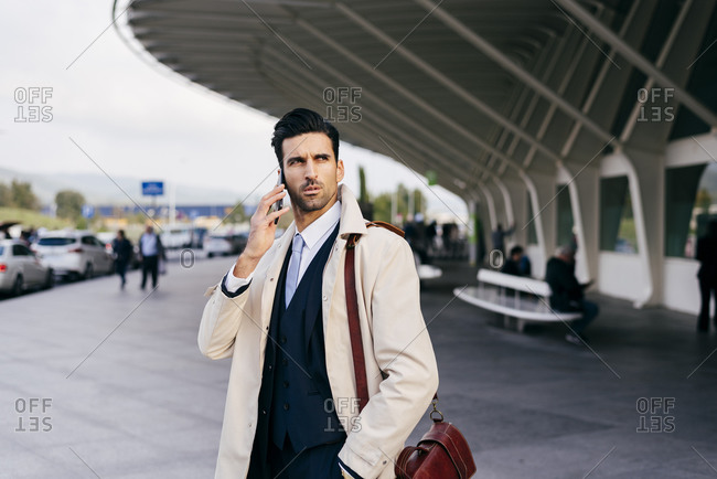 Busy man with dark hair in suit and coat speaking on phone while standing near airport terminal at daytime