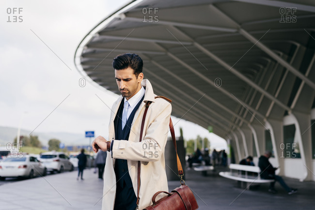 Man with dark hair in suit and coat looking your watch while standing near airport terminal at daytime