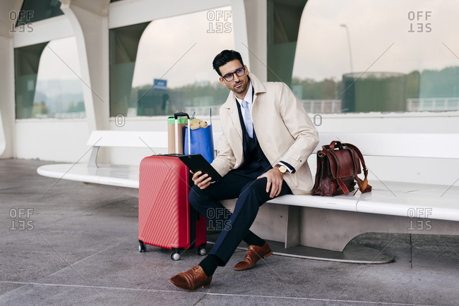 Confident man with hairstyle in stylish formal clothes with suitcase and shopping bags sitting on bench near airport and using tablet