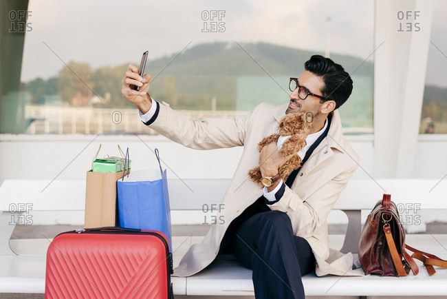 Smiling man with hairstyle in trendy formal clothes sitting on bench with suitcase and shopping bags and holding toy dog and taking selfie against modern building at daytime