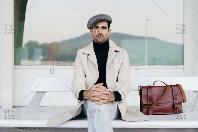 Confident man with beard in trendy clothes sitting on white bench with bag and looking at camera against modern building with big window