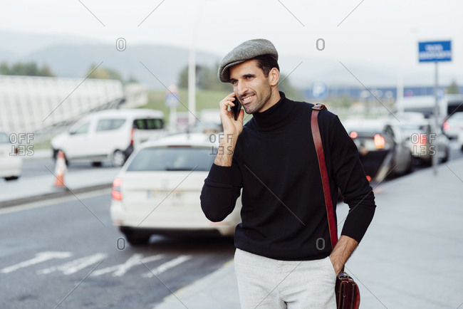 Smiling man with beard in trendy clothes talking on smartphone while standing on street near asphalt road with parked cars at daytime