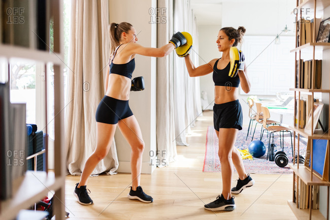 Side view of fit female fighter in gloves and personal coach in boxing mitts standing in living room and preparing for workout