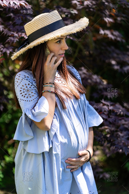 Beautiful pregnant female in stylish dress and straw hat touching tummy gently while standing against blooming tree and talking on smartphone in summer garden