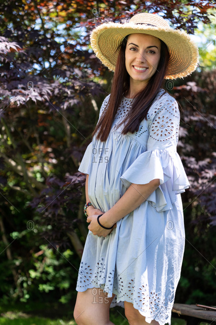 Happy pregnant female in stylish summer dress and hat hugging belly and looking at camera while standing against blooming tree in garden