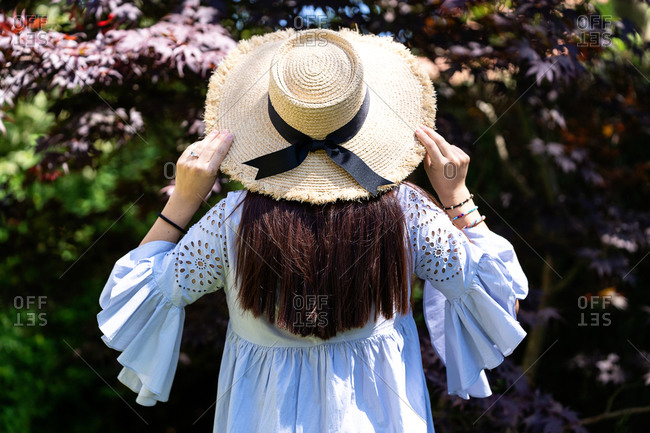 Back view of unrecognizable brunette in charming lilac dress and straw hat standing against blooming trees in garden
