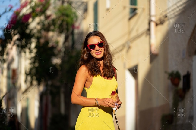 Delighted young long haired brunette with red sunglasses enjoying tasty colorful ice cream in waffle cone in the street in summer day looking at camera