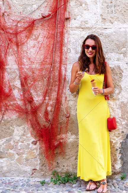 Smiling young female in bright yellow sundress and sunglasses standing amidst leafless red tree branches against shabby stone wall of old building