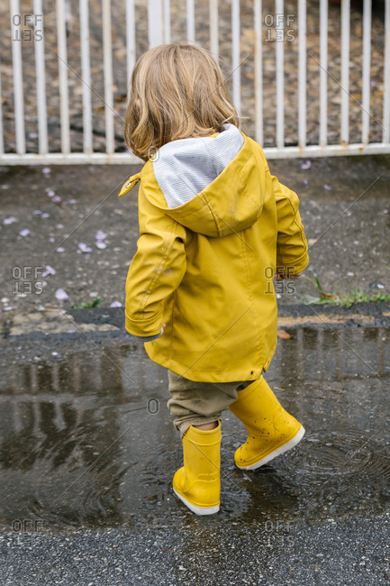 Back view of little playful kid in yellow raincoat and rubber boots walking in puddle and splashing water while having fun after rain