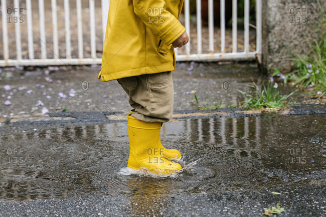 Cropped little playful kid in yellow raincoat and rubber boots walking in puddle and splashing water while having fun after rain