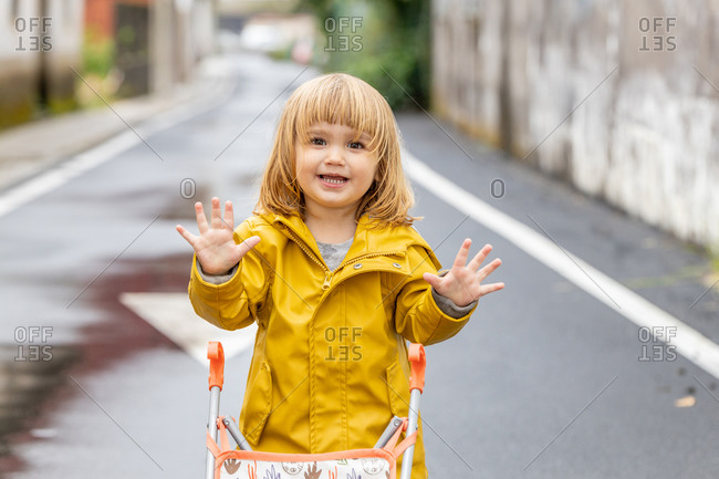 Cheerful little girl in yellow raincoat and rubber boots running with toy baby carriage along wet road after rain looking at camera
