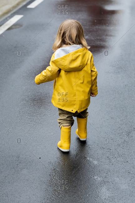 Back view of cute little child in vivid yellow raincoat and rubber boots standing on wet asphalt road after rain