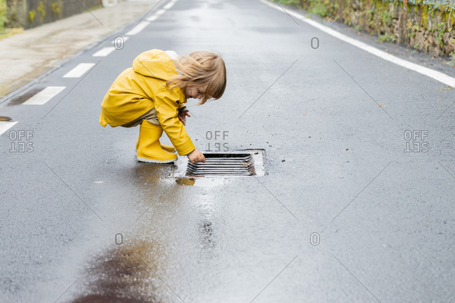 Side view of curious little child in vivid yellow raincoat and rubber boots standing on wet asphalt road after rain