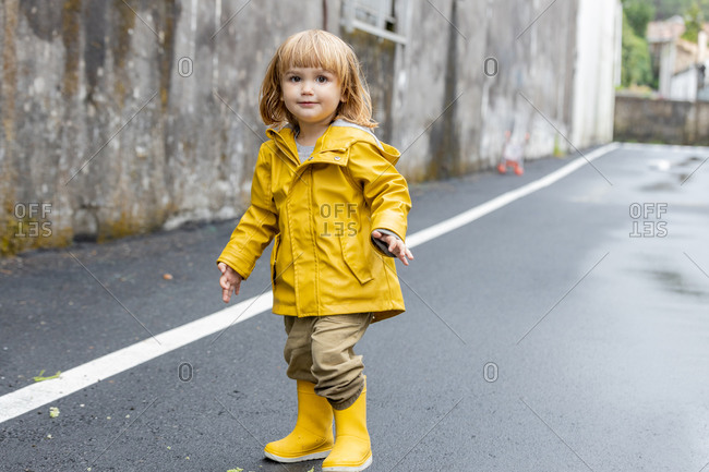 Cute little child in vivid yellow raincoat and rubber boots standing on wet asphalt road after rain looking at camera
