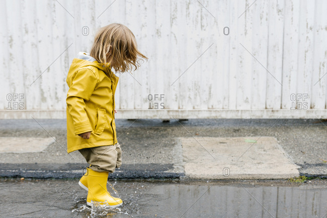 Side view of little playful kid in yellow raincoat and rubber boots walking in puddle and splashing water while having fun after rain